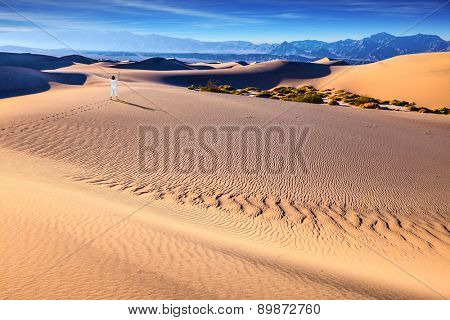 Orange sand dunes in Death Valley, California. Middle-aged woman in white performs Yoga in the desert