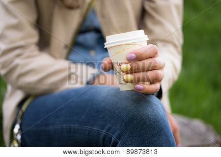 A Disposable Coffee Cup In A Female Hand Closeup