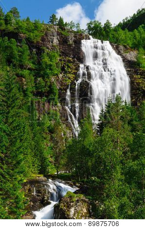 Tall Norwegian Waterfall And Coniferous Forest