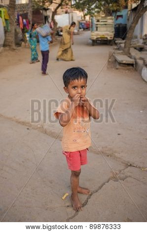 KAMALAPURAM, INDIA - 02 FEBRUARY 2015: Indian child standing in village street while people pass in the background.
