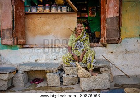 KAMALAPURAM, INDIA - 02 FEBRUARY 2015: Indian female vendor siiting outside of her shop in a town close to Hampi