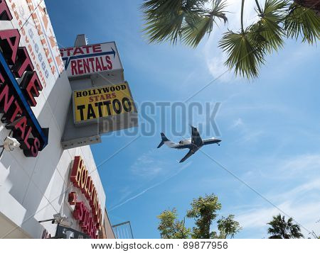 LOS ANGELES - April 29, 2015: Airplane plane flying over LA, framed inside signs and palm trees.