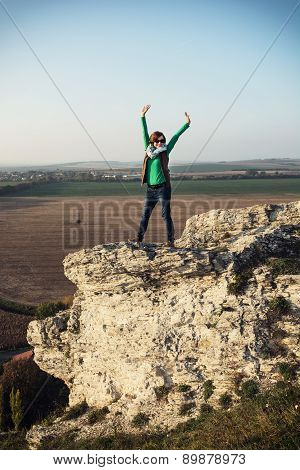 Young Caucasian Positive Woman Posing On The High Rock