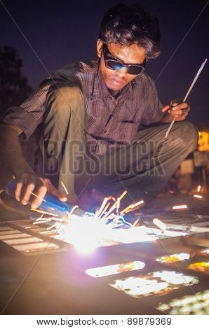 KAMALAPURAM, INDIA - 02 FEBRUARY 2015: Indian worker welding heavy metal parts on street in dusk
