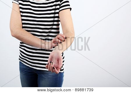 Woman has itch on gray background