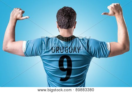 Uruguayan soccer player on blue background
