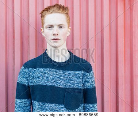 Young redhead man in a sweater and jeans standing next to red wall