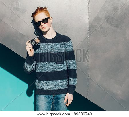 Young redhead man in a sweater and jeans standing next to green grea wall and taking photos vintage