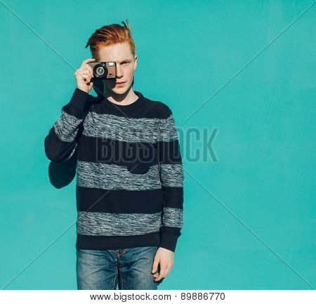 Young redhead man in a sweater and jeans standing next to turquoise wall and taking photos vintage c