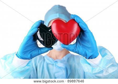 Decorative heart in doctors hands, on light background