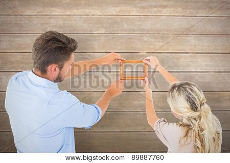 Attractive young couple hanging a frame against wooden surface with planks