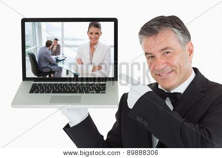 Smiling marketing manager standing in conference room against smiling waiter pointing us something on a laptop