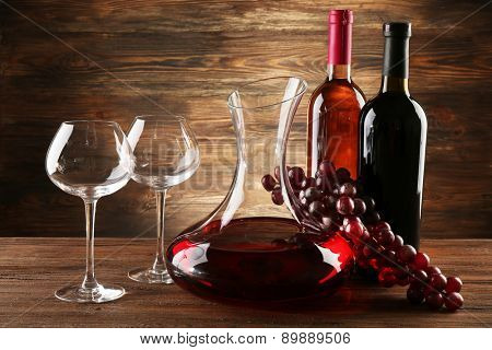 Glass carafe of wine on wooden background