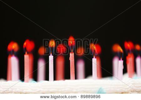 Candles on birthday cake on black background