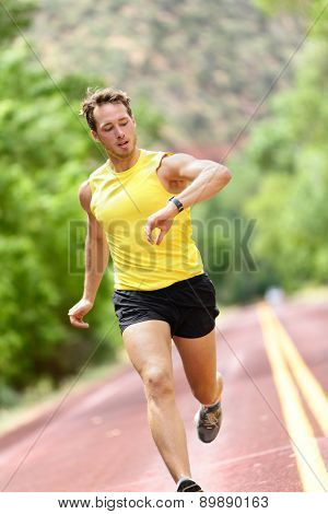 Runner looking at heart rate monitor smart watch while running. Man jogging outside looking at his sports smartwatch during workout training for marathon run. Fit male fitness model in his 20s.