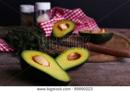 Sliced avocado with lime and herb on cutting board with knife on wooden table on black background