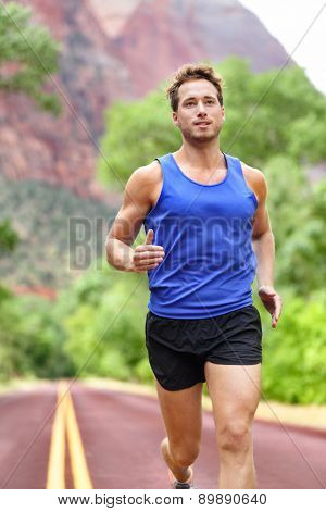 Sport and fitness runner man running on road training for marathon run doing sprint interval workout outdoors in summer. Male athlete sports model fit and healthy smiling with aspirations.