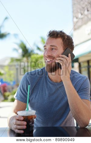 Man on cafe using smartphone talking on mobile cell smart phone drinking iced coffee in summer. Handsome young casual man using smartphone smiling happy sitting outdoors. Urban male in his 20s.