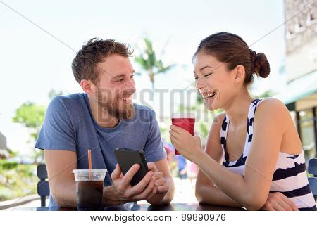 Couple on cafe looking at smart phone app pictures drinking coffee in summer. Young urban man using smartphone smiling happy to casual asian woman sitting outdoors. Friends in late 20s