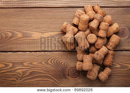 Heap of champagne corks over rustic wooden table background with copy space