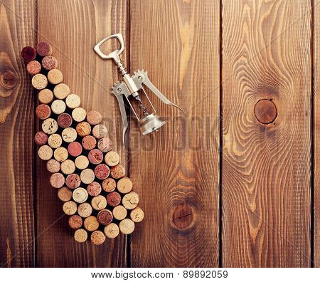 Wine bottle shaped corks and corkscrew over rustic wooden table background. View from above with copy space