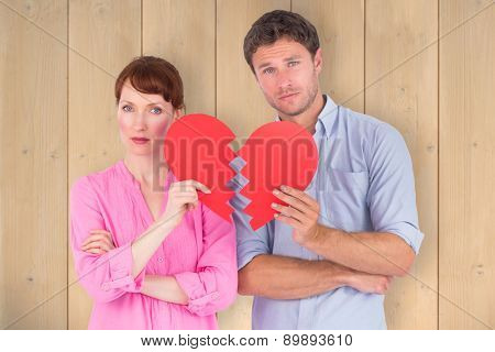 Couple holding a broken heart against wooden planks