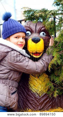Portrait of nine- year-old girl with wooden bear