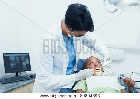 Female dentist examining boys teeth in the dentists chair