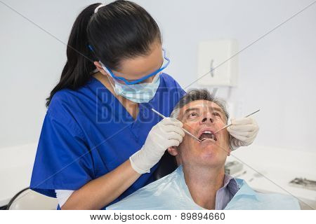 Dentist examining a patient with tools in dental clinic