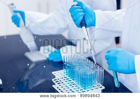 Science students using pipettes to fill test tubes at the university