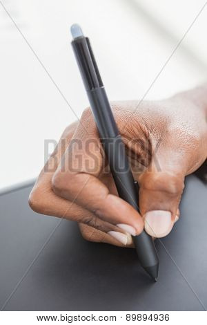 Hand of designer using stylus and digitizer in the office