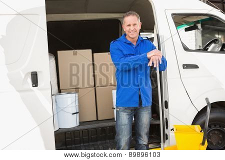 Cleaning agent standing and smiling at camera in front of his van