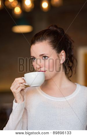 Pretty brunette sipping cup of coffee at the cafe