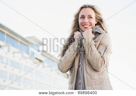 Portrait of smiling blonde in warm clothes in the city