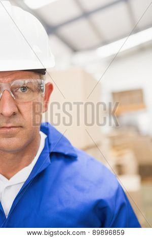 Close up portrait of worker wearing hard hat in the warehouse