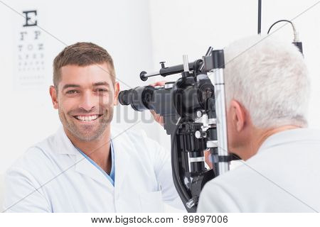 Portrait of happy male optometrist examining senior patients eyes through phoropter in clinic