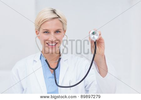 Portrait of confident female doctor holding stethoscope in clinic