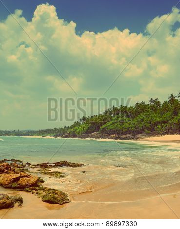beautiful landscape with sea waves on tropical beach with stones and rocks - vintage retro style