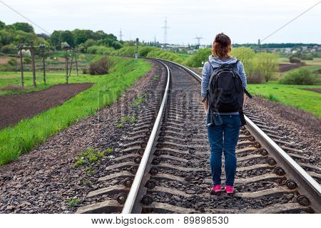 a girl sitting on rails stops a train