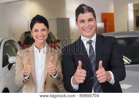 Business team giving thumbs up at new car showroom