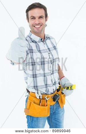 Portrait of happy handyman gesturing thumbs up over white background