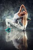 picture of wall-stone  - Young woman modern dancer stretching legs - JPG