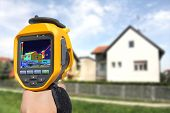 stock photo of thermal  - Recording Heat Loss at the House With Infrared Thermal Camera - JPG