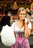 stock photo of candy cotton  - Beautiful woman wearing a traditional Dirndl dress with cotton candy floss at the Oktoberfest - JPG