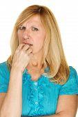 stock photo of fingernail  - Single isolated worried adult female biting fingernails - JPG