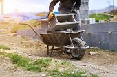 stock photo of wheelbarrow  - Bricklayer taking another brick from a wheelbarrow - JPG