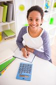 picture of mulatto  - Young pretty smiling mulatto schoolgirl sitting at the table and writing a homework on colorful background - JPG