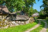 image of old stone fence  - Mossy stone fence and old boat as decoration - JPG
