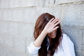 image of shy girl  - Shy brunette girl covering her face with a grey wall of background - JPG