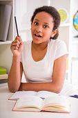 stock photo of mulatto  - Young pretty mulatto schoolgirl sitting at the table and holding a pencil in hand on colorful background - JPG